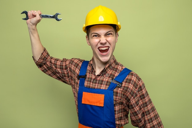 Young male builder wearing uniform holding open-end wrench isolated on olive green wall