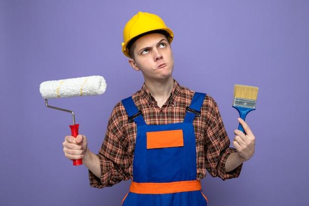 紫色の壁に分離されたローラーブラシと均一な保持ペイントブラシを身に着けている若い男性ビルダー