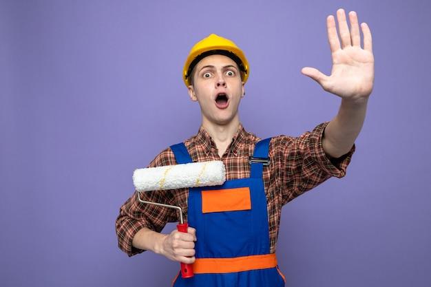 紫色の壁に分離された均一な保持ローラーブラシを身に着けている若い男性ビルダー