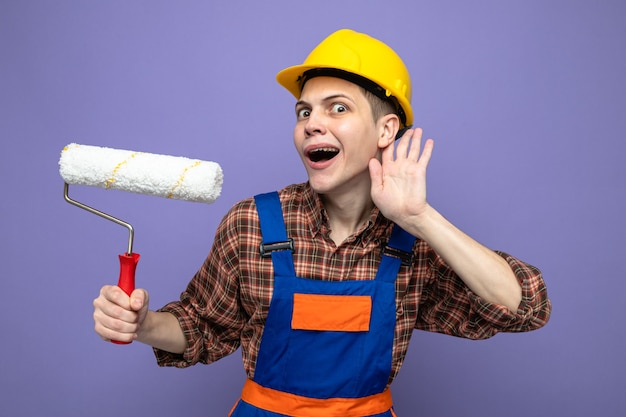 Young male builder wearing uniform holding roller brush isolated on purple wall
