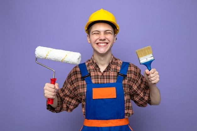紫色の壁に分離されたペイントブラシと均一な保持ローラーブラシを身に着けている若い男性ビルダー