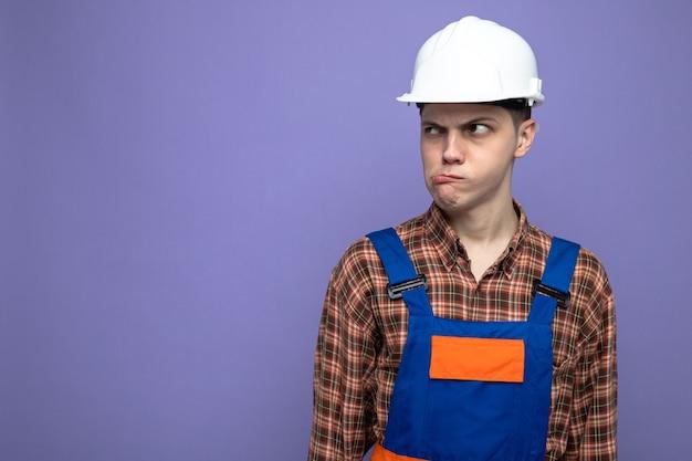 コピースペースと紫色の壁に分離された制服を着ている若い男性ビルダー
