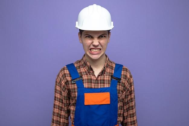 보라색 벽에 고립 된 유니폼을 입고 젊은 남성 빌더