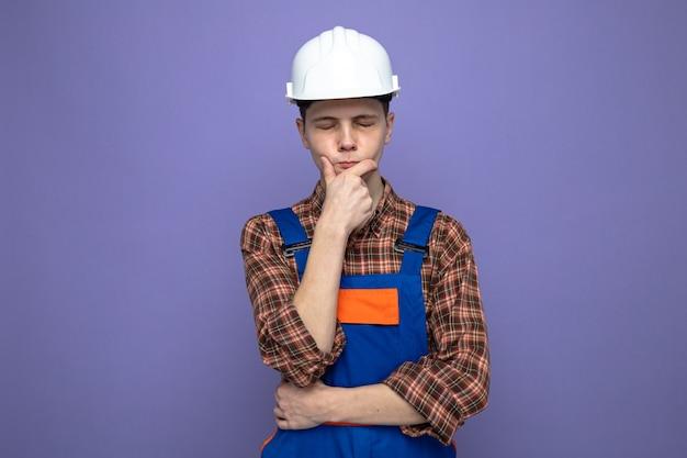 紫色の壁に分離された制服を着ている若い男性ビルダー