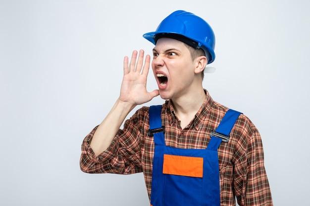 Giovane costruttore maschio che indossa l'uniforme isolata sulla parete bianca con lo spazio della copia