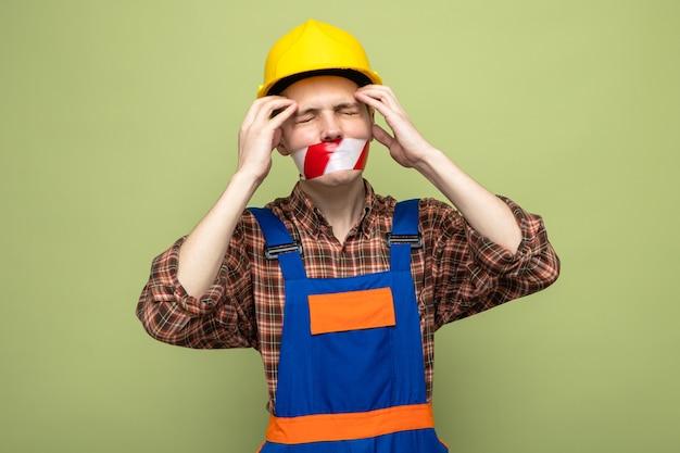 올리브 녹색 벽에 덕트 테이프가 분리된 균일한 밀봉된 입을 입은 젊은 남성 건축업자