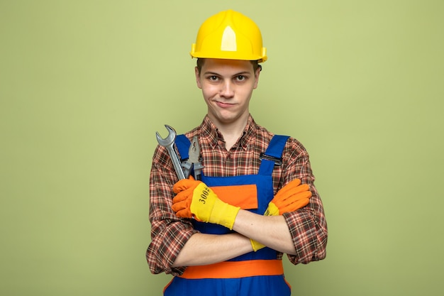 Giovane costruttore maschio che indossa l'uniforme con i guanti che tengono la chiave aperta isolata sulla parete verde oliva
