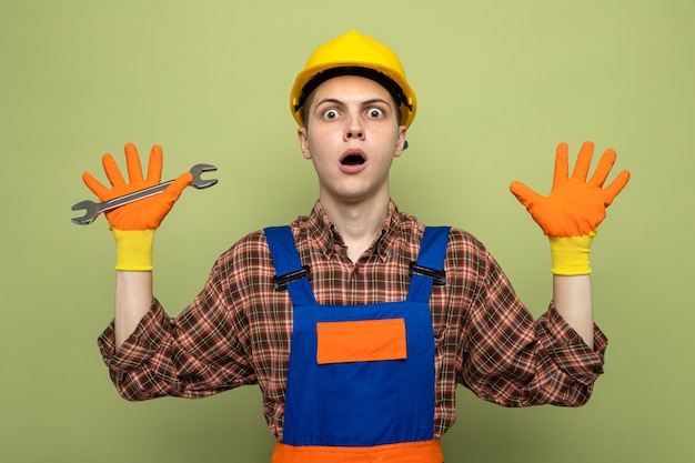 Young male builder wearing uniform with gloves holding open-end wrench isolated on olive green wall