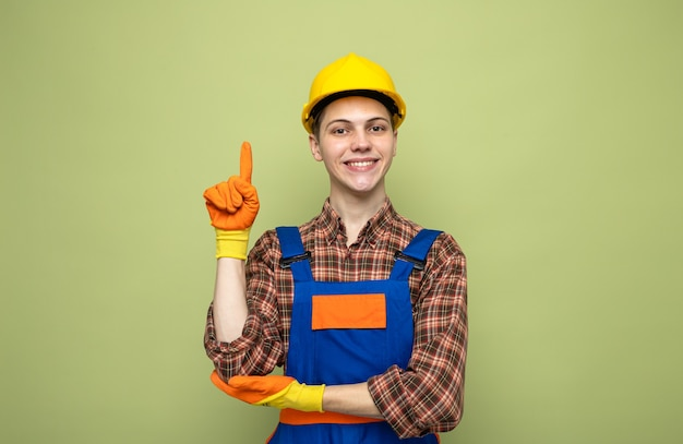 Young male builder wearing uniform with gloves isolated on olive green wall