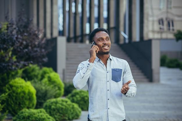 젊은 남성 사업가, 캐주얼한 옷차림으로 휴대폰으로 쾌활하게 이야기하고 프리랜서 직원은 동료들과 행복하게 대화합니다
