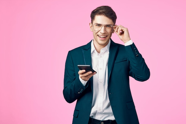 Young male businessman in glasses with a phone on a
