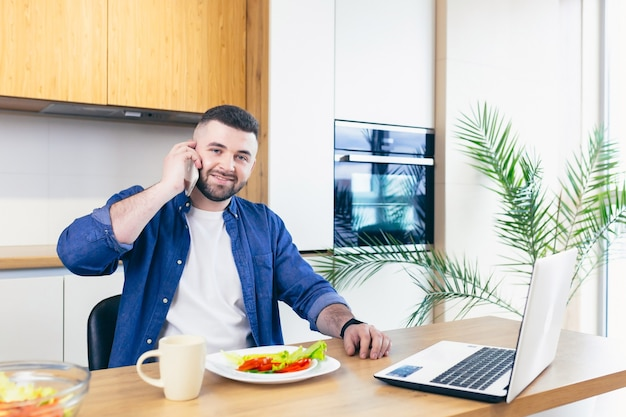 집에서 아침을 먹고 노트북에서 사업을하는 젊은 남성 사업가