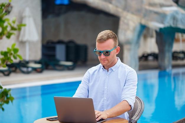 サングラスをかけた若い男性実業家は、プールの近くのテーブルに座っているラップトップで働いています。リモートワーク。フリーランサー