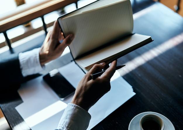 若い男性ビジネスマンはペーパーでテーブルに座っているし、コーヒーを飲み、窓の外に見える