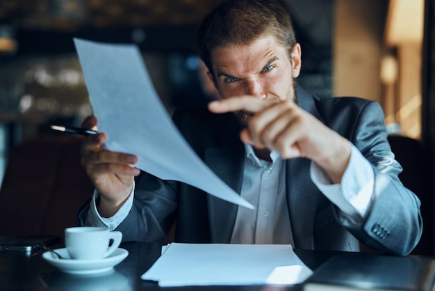 Young male businessman sits at a table with papers and drinks coffee, looks out the window
