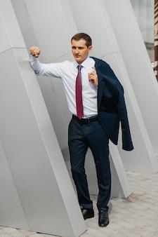 若い男性実業家は、オフィスビルの近くでポーズをとって笑って肩にジャケットを運ぶ仕事から家に帰る