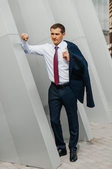 Young male businessman walking home from work carrying jacket on shoulder smiling posing near office building