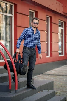 Young male businessman with a beard walks with a bag on the steps. handsome guy in shirt and glasses