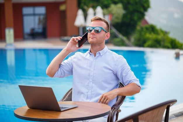 プールのそばに座っているラップトップを持つ若い男性実業家。オープンワークプレイス。フリーランサーのコンセプト。オンラインショッピング。休暇の仕事