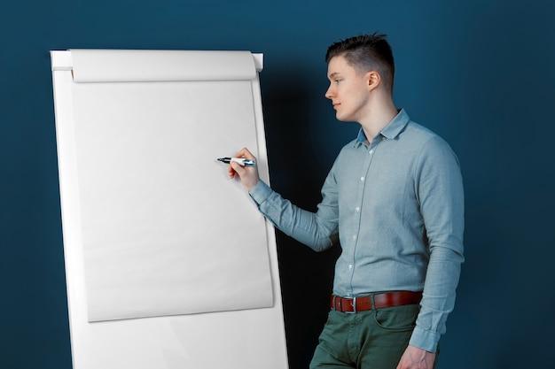 若い男性実業家は、黒板に鉛筆で書いています。