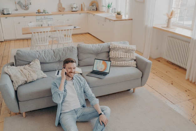 Young male bussiness owner receiving call from his worker, happy with his company profits, smiling after checking report on laptop, sitting on carpet while resting against sofa. freelance concept