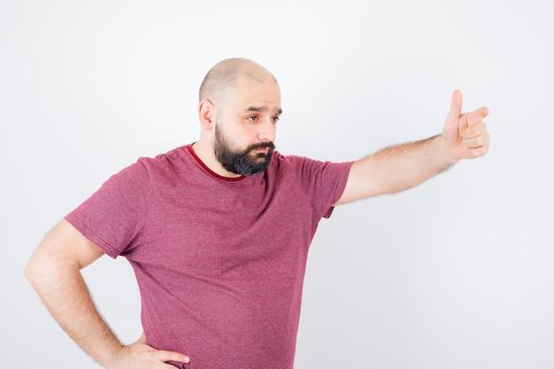 ピンクのtシャツの正面図で誰かを手で呼び出す若い男性。