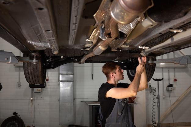 Молодой мужчина автомеханик в униформе, проверяет машину в автосервисе