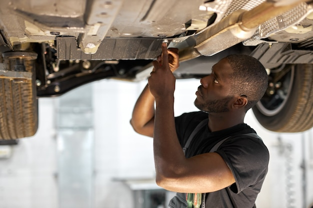 Young male car mechanic in uniform checking car in automobile service with lifted vehicle