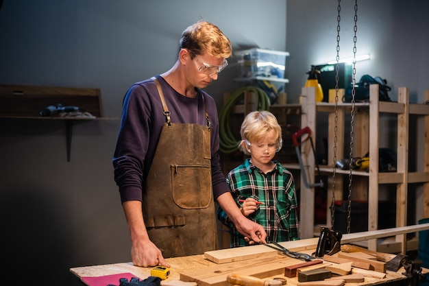 A young male carpenter is teaching woodwork to a young boy in his workshop.