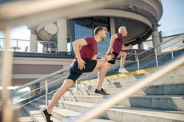階段で成熟した男性に追いつく若い男性