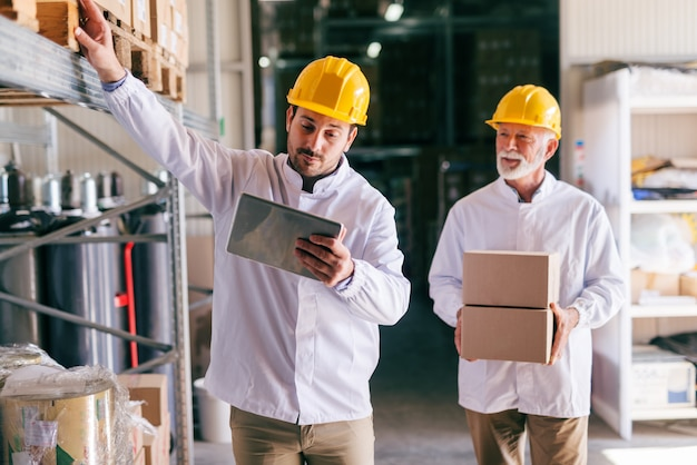 Young male caucasian worker using tablet while standing in warehouse.