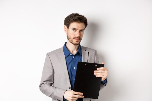 Молодой мужской генеральный директор держа доску сзажимом для бумаги с документами и смотря камеру, проверяя офис, стоя на белой предпосылке.