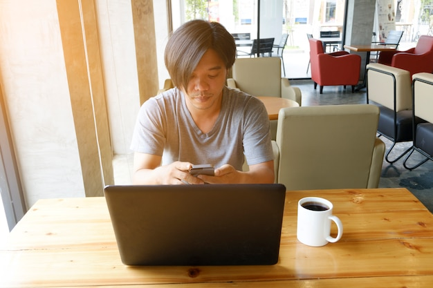 Young male chatting on mobile phone while sitting in cafe , man reading text message during work on net-book in comfortable coffee shop