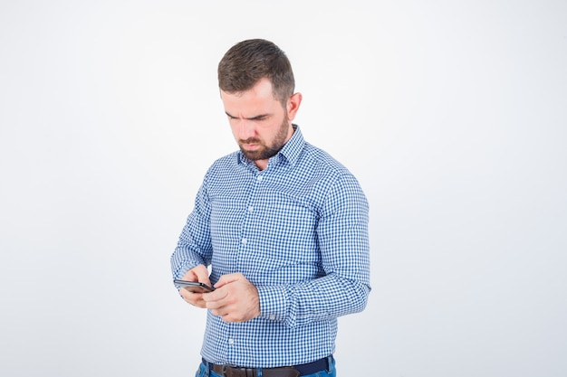 シャツ、ジーンズ、物思いにふける、正面図で携帯電話でチャットする若い男性。