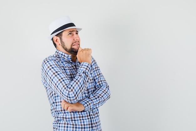 Giovane maschio in camicia a quadri, cappello che osserva in su nella posa di pensiero e che sembra riluttante, vista frontale.