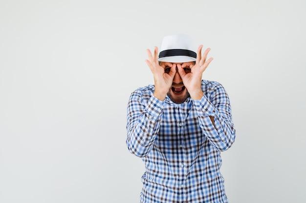 Giovane maschio in camicia a quadri, cappello che mostra il gesto degli occhiali e che sembra divertente, vista frontale.