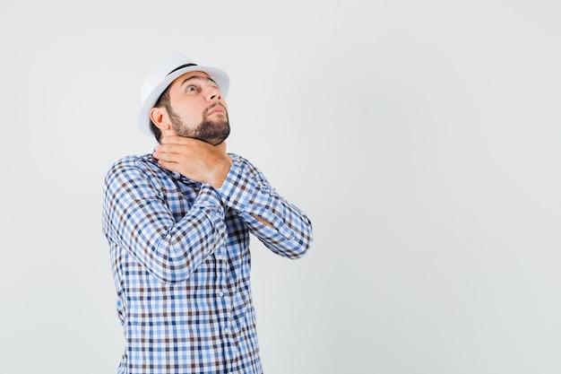 Giovane maschio in camicia a quadri, cappello che soffre di mal di gola, soffocamento e malessere, vista frontale.