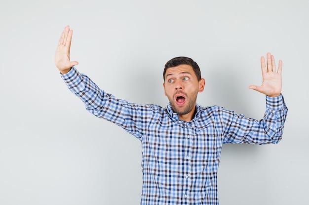 Giovane maschio in camicia a quadri che grida mentre fa il gesto di resa e sembra spaventato