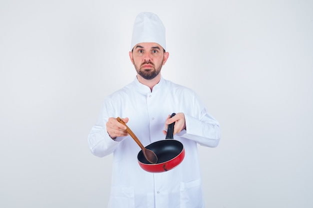 Young male chef holding empty frying pan with wooden spoon in white uniform and looking downcast. front view.