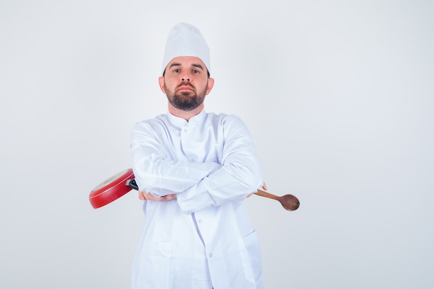 白い制服を着て腕を組んで立って、自信を持って、正面図を見て、フライパンと木のスプーンを保持している若い男性シェフ。