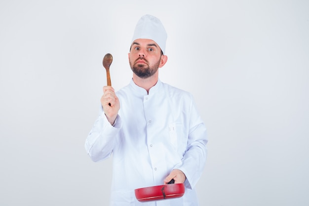 Young male chef holding frying pan and wooden spoon in white uniform and looking thoughtful. front view.