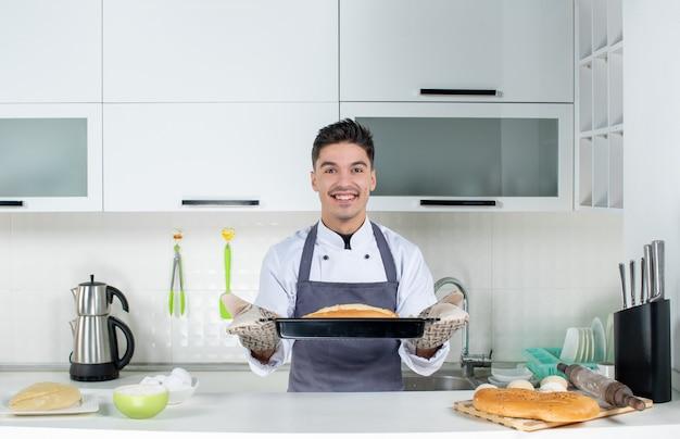 홀더를 착용하고 흰색 부엌에서 갓 구운 빵을 들고 테이블 뒤에 서있는 유니폼을 입은 젊은 남성 요리사