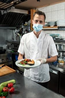 白い制服を着た若い男性シェフとキッチンテーブルの上に蒸したみじん切り野菜と揚げ鮭を保持している保護マスク