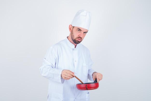 白い制服を着た若い男性シェフが木のスプーンで食事を混ぜて物思いにふける、正面図。