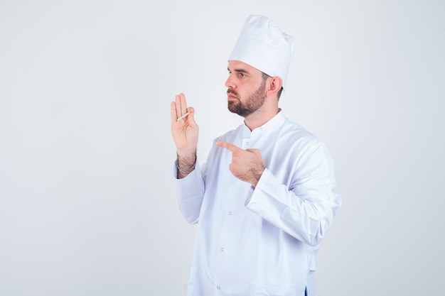 흰색 유니폼에 담배를 가리키는 사려 깊은 찾고 젊은 남성 요리사. 전면보기.