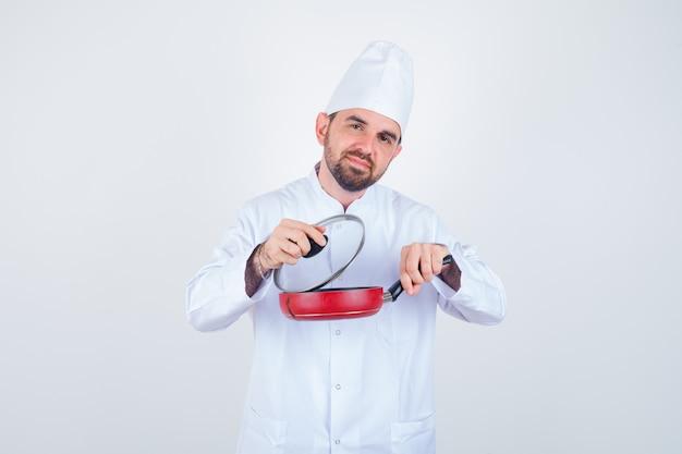 Giovane cuoco unico maschio che rimuove il coperchio dalla padella in uniforme bianca e che sembra curioso, vista frontale.