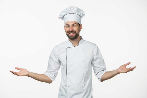 Young male chef in uniform standing against white background shrugging