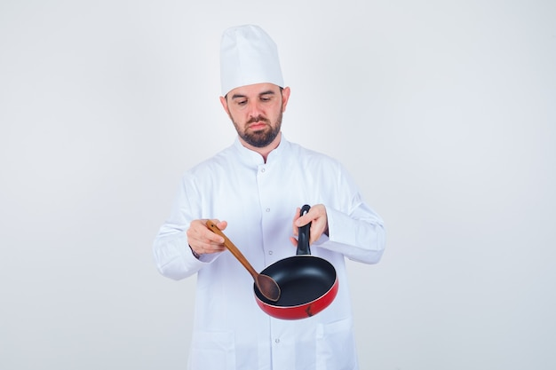 Young male chef in white uniform holding empty frying pan with wooden spoon and looking downcast , front view.