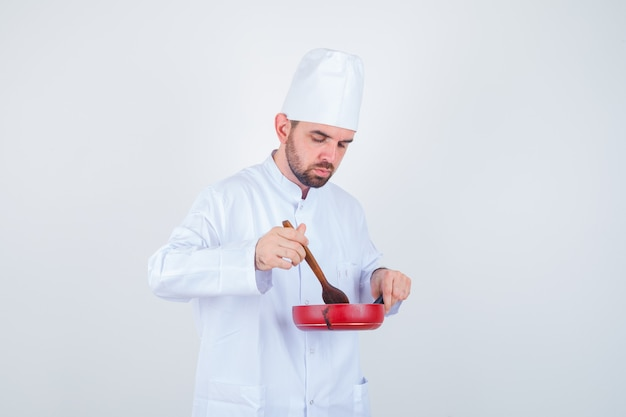 Young male chef in white uniform mixing meal with wooden spoon and looking curious , front view.
