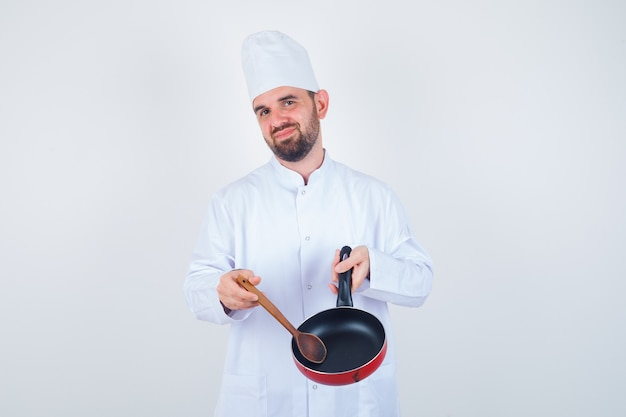 Young male chef in white uniform showing empty frying pan with wooden spoon and looking disappointed , front view.